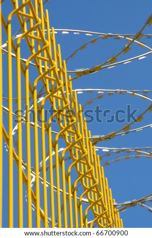 bright yellow fence with barbed wire on a background of blue sky - stock photo