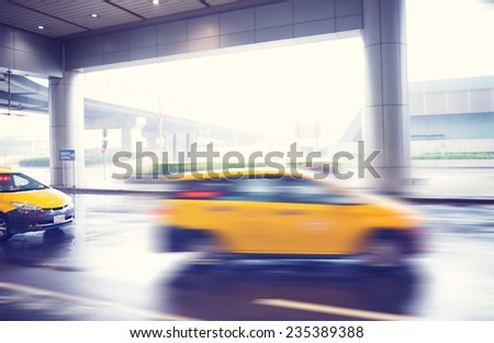 Bright yellow iconic taxi cab speeding past the illuminated entrance of an airport terminus building with motion blur of the car