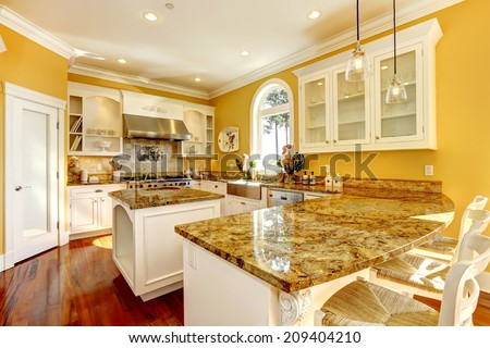 Bright yellow kitchen interior in luxury house with granite tops and kitchen island. - stock photo