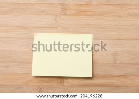 Bright Yellow paper blank with pin on wooden board  - stock photo