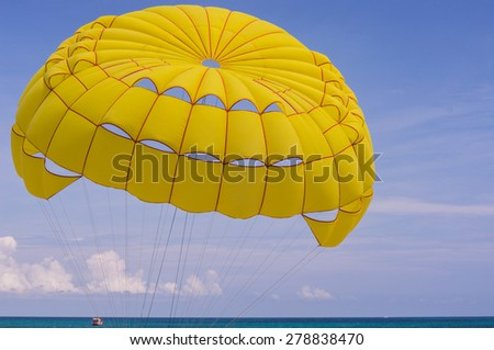Bright yellow parachute carries it's riders from the sandy beach over the blue waters of the Andaman Sea - stock photo