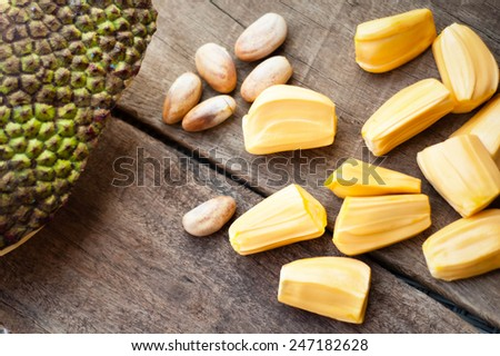 bright yellow pieses of jackfruit on wooden background.
