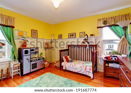 Bright yellow room for kids with toys - stock photo
