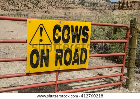 Bright, yellow sign warning motorists that they are entering a section of road that is open range and may have cows on it