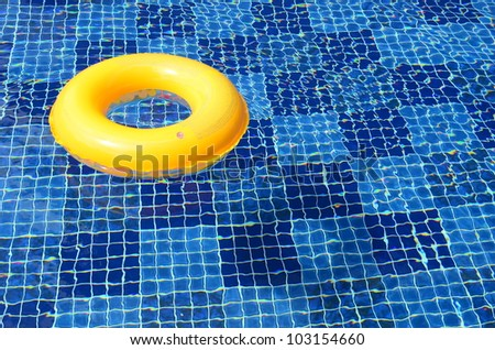 bright yellow swim ring in the deep blue swimming pool - stock photo