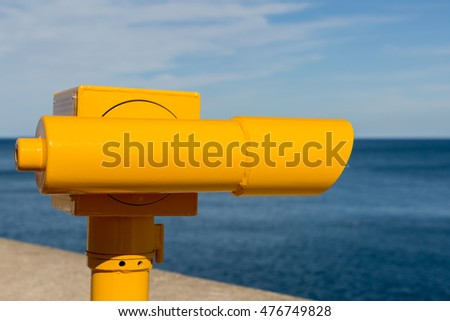 Bright yellow telescope used to view the ocean