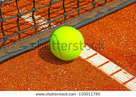 Bright yellow tennis ball on the court - stock photo