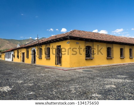 Bright yellow typical colonial style building in Antigua, Guatemala - corner perspective - stock photo