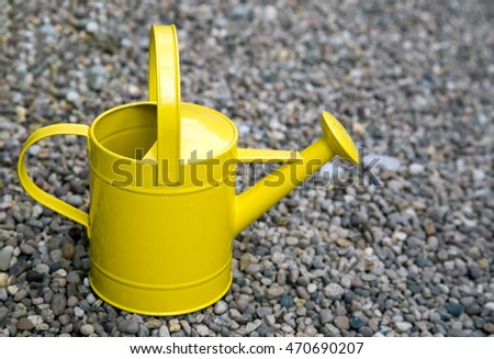 Bright yellow watering can on gravel