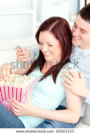 Bright young couple lying on the sofa with popcorn and remote at home