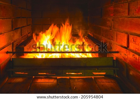 brightly burning flame of fire in the fireplace of brick - stock photo