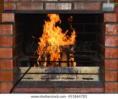 brightly burning flame of fire in the fireplace of brick