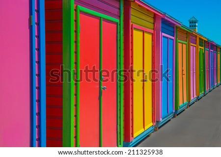 brightly colored beach huts - stock photo