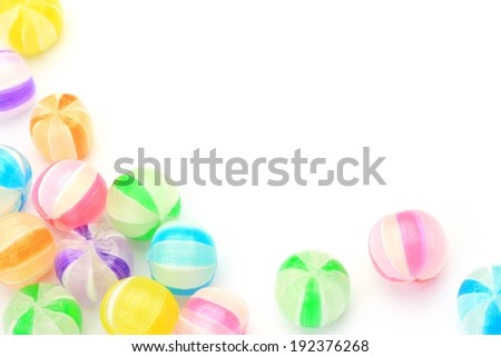 Brightly colored beads or candy set against a white background. - stock photo