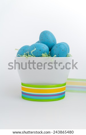 Brightly colored blue eggs in a white bowl encircled by vibrant ribbon on a white background - stock photo