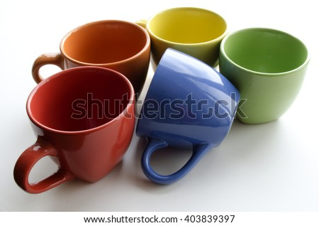 brightly colored ceramic cups on a light background