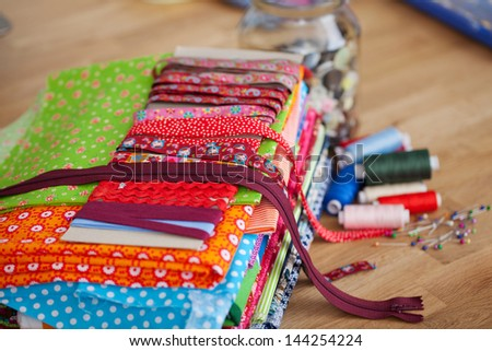 Brightly colored collection of zips, borders and textiles neatly folded and displayed on a wooden counter in the studio of a seamstress - stock photo