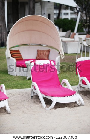 Brightly colored deck chairs at a tropical resort - travel and tourism image. - stock photo