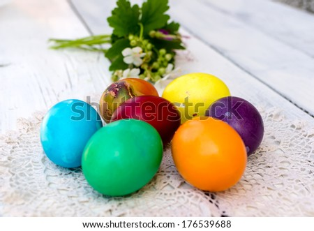 Brightly colored Easter eggs decorated with white geraniums - stock photo