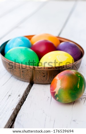 Brightly colored Easter eggs in a beautiful copper bowl - stock photo