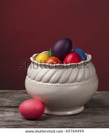 Brightly colored Easter Eggs with a red background on a wooden table. Simple yet beautiful traditional decoration. - stock photo