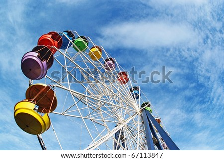 Brightly colored Ferris wheel against the blue sky - stock photo