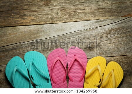 Brightly colored flip-flops on wood. Family vacation - stock photo