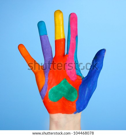 Brightly colored hand on blue  background close-up