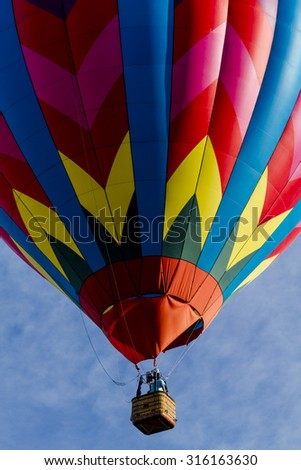 Brightly colored hot air balloon against blue morning sky just after take off - stock photo