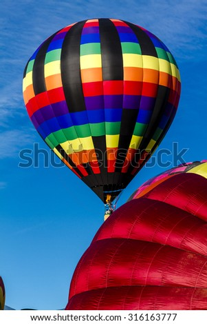 Brightly colored hot air balloons against blue morning sky on the ground and just after take off