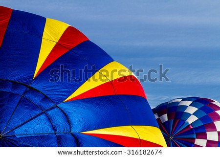 Brightly colored hot air balloons against blue morning sky on the ground before take off - stock photo