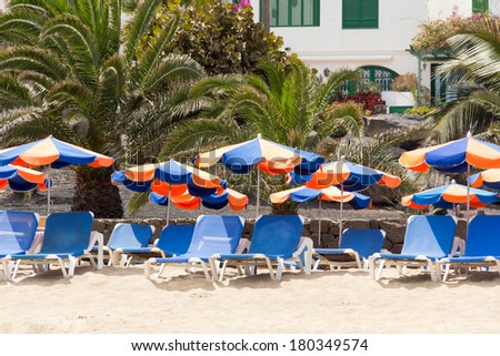 Brightly colored parasols and sun loungers set up on tropical beach with palm trees and   white building as a back drop - stock photo