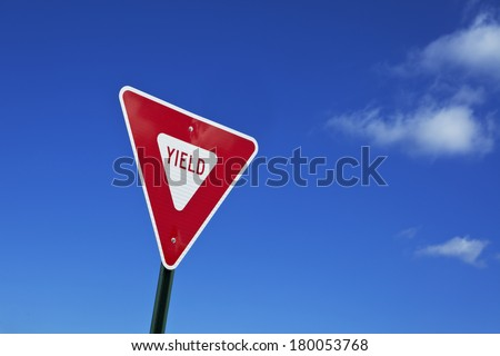 Brightly colored red and white yield sign against dark blue sky with clouds. Some clouds are reflected in the yield sign. Plenty of space for your copy. Photographed on a public highway. - stock photo