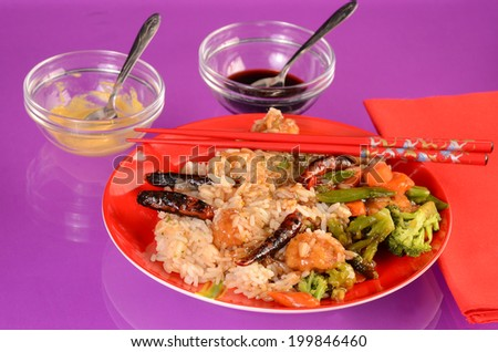 Brightly colored setting with General Tso chicken on red plate against purple reflective background with chopsticks and condiments. - stock photo