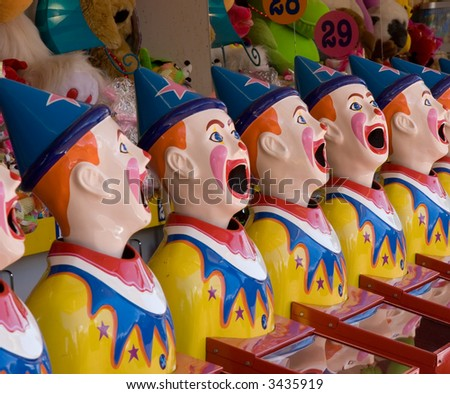 Brightly colored sideshow clowns at a fair
