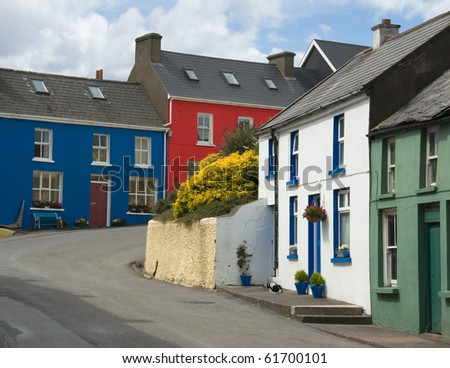 Brightly colored street houses in the village of Eyeries, West Cork, Ireland, on a sunny summer day. Each home in this area is typically painted a different hue to distinguish it from its neighbors. - stock photo