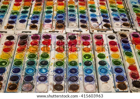 Brightly colored watercolor pans lined up in rows showing a bright spectrum of color