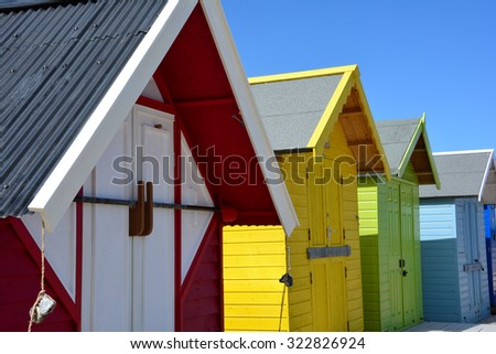 Brightly coloured beach huts by the sea - stock photo