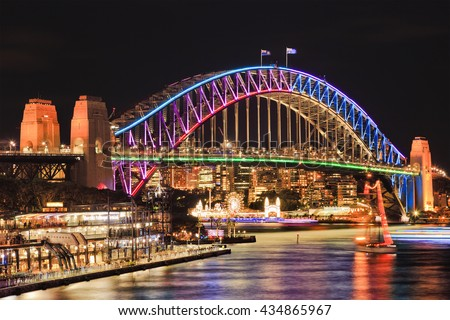 Brightly illuminated arch side of landmark Sydney Harbour Bridge after sunset reflecting lights in blurred still waters of bay.
