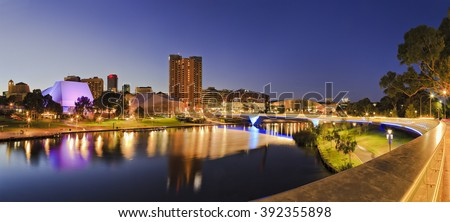 brightly lit Adelaide city CBD with foot bridge across Torrens river. Illumination reflecting in calm waters at sunrise.