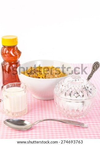 Brightly lit breakfast scene; honey and milk on pink gingham table with cereal and vintage crystal sugar bowl.