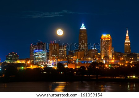 Brightly lit Cleveland Ohio under a just risen full moon - stock photo