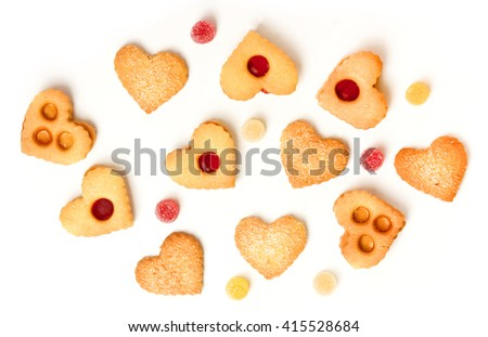 Brightly lit heart-shaped tea cookies and gum drops on white background - stock photo