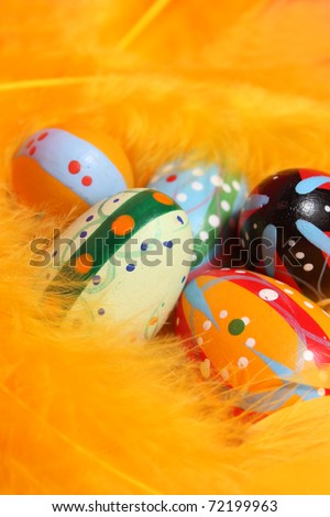 Brightly painted eggs in the yellow feathers