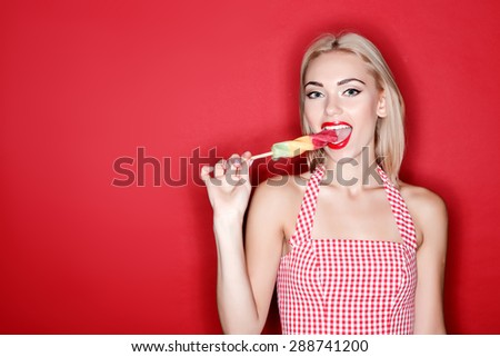 Brightness of moment. Nice youthful blond-haired girl keeping candy and going to taste it on isolated red background - stock photo