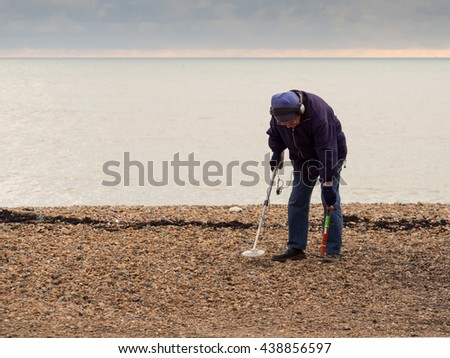 BRIGHTON, ENGLAND - FEBRUARY 10, 2016: A man with a metal detector combs the beach for dropped money and other valuable items.