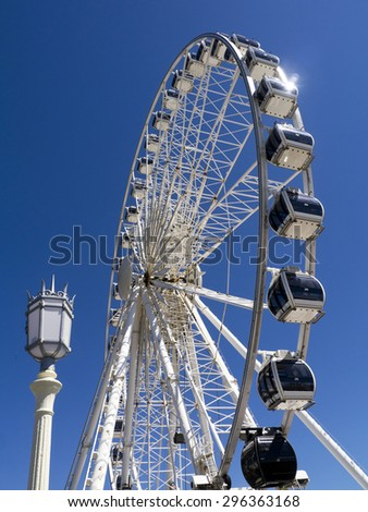 Brighton Eye Ferris Wheel; silhouetted against deep blue sky with street lamp in foreground - stock photo