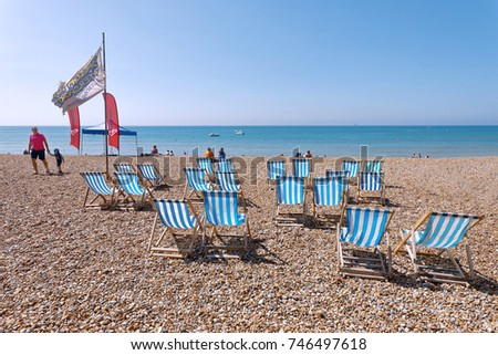 BRIGHTON, GREAT BRITAIN   JUN 17, 2017: Classic Deckchairs, People  Sunbathing And
