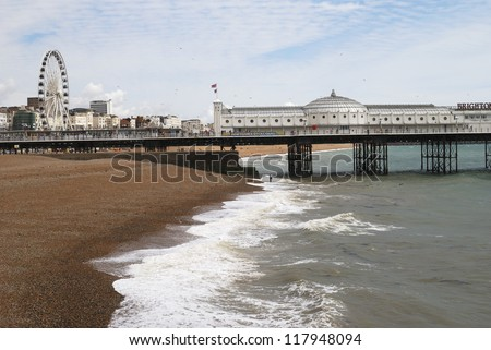 Brighton pier and wheel viewed from across the shingle beach. East Sussex. England - stock photo