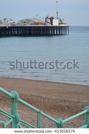 Brighton Pier in the background with turquoise railing in foreground - stock photo